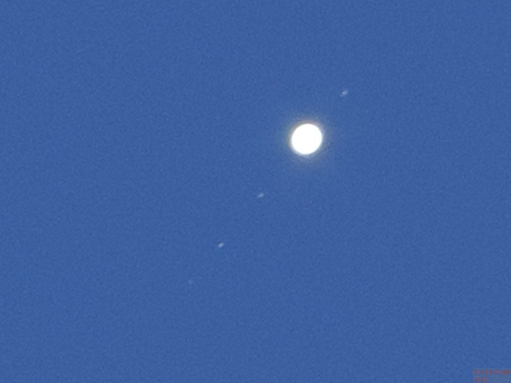 Jupiter and four moons in a blue sky